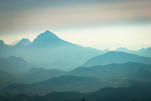 Scenic View Of Mountains Against Hazy Sky