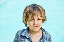 Child Scowling And Looking At Camera In Sunlight
