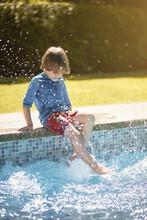 Anonymous Little Boy Splashing Water In Pool With Feet
