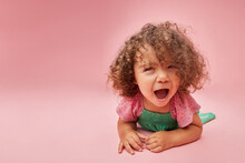 Cute Upset Little Girl Sitting On Pink Background