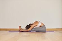 Anonymous Woman Showing Caterpillar Pose On Yoga Mat
