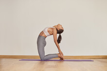 Woman Standing In Camel Pose On Yoga Mat Indoors