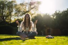 Smiling Woman Meditating In Lotus Pose In Sunny Park