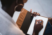 Black Woman Making Notes In Notebook