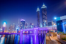 Illuminated Waterfall Bridge In Downtown Dubai At Night With Thousands Of Small Lights On High Skyscrapers. Popular Tourist Attractions In UAE