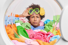 Serious Attentive Young Woman With Afro Hair Wears Snorkeling Mask Poses Through Washing Machine Door Surrounded By Multicolored Laundry And Detergent Does Laundry At Home. Housekeeping Concept