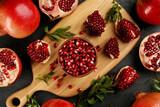 Fototapeta Kawa jest smaczna - Delicious ripe pomegranates on black table, flat lay