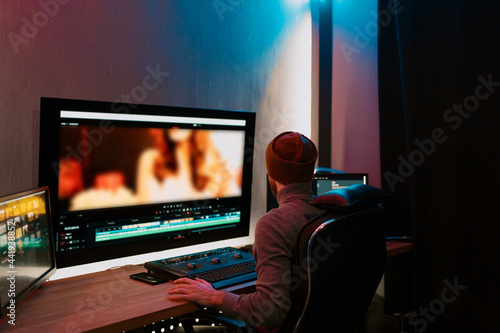Fotografering Attractive Male Video Editor Works with Footage or Video on His Personal Computer, he Works in Creative Office Studio or home