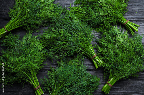 Tela Bunches of fresh dill on black wooden table, flat lay