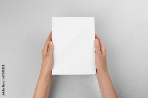 Woman holding book with blank cover on light grey background, closeup. Space for design