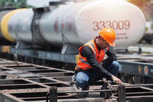 Worker On The Station. Worker On The Railway. Worker Sitting On Bogie With Oil Tank On Background.