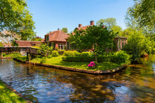 """The Famous Village Of Giethoorn In The Netherlands With Traditional Dutch Houses, Gardens And Water Canals And Wooden Bridges Is Know As """"Venice Of The North"""""""