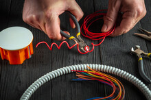Repair Of Electrical Equipment In The Workshop Of A Master Electrician. Close-up Of The Hand Of Master During Work