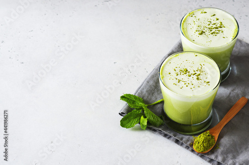 Fototapeta Green smoothie mint or matcha latte in glass