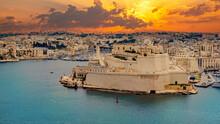 Panorama Of A Romantic Scene Of The Capital Valletta Illuminated At Dusk And The Blue Sea In Malta