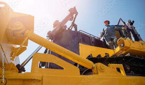 Fotografia Industrial portrait of working man, excavator driver climbs into cab to perform