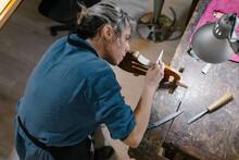 Craftswoman Making Violin In Workshop