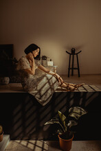 Woman Sitting In Room With Plants