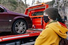 Woman In Mask Standing Near Car Towed On Truck