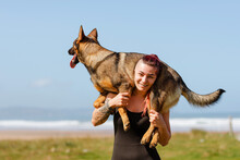 Smiling Sportswoman Carrying German Shepherd Under Blue Sky
