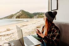 Traveling Freelancer Using Smartphone And Working In Van