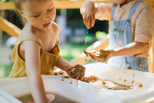 Happy Children Play With Sand And Water In Sensory Baskets On The Outdoor Sensory Table, Sensory Early Development, Montessori. Baby Hands With Sand And Water Close Up, Soft Focus