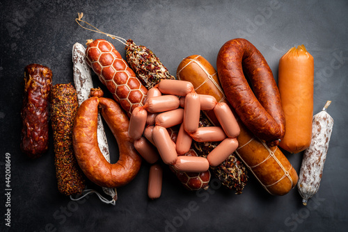 Set of different types of sausages, salami and smoked meat with basil and spices on a black background Fototapet