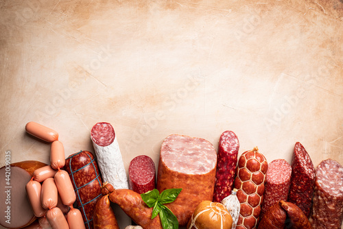 Billede på lærred Set of different types of sausages, salami and smoked meat with basil and spices on light background