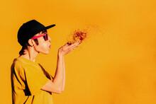 Informal Lady Blowing Confetti Near Yellow Wall