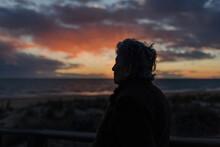 Senior Lady Admiring Sunset Over Ocean From Boardwalk
