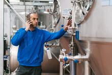 Engineer Speaking On Smartphone Against Fermentation Tanks In Brewery
