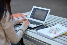 Young Female Student Studying On Her Laptop Outdoors