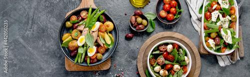 Fotografering Assorted salads on dark gray background. Seasonal food concept.