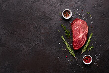 Fresh Raw Marbled Beef Rib Eye Steak, Herbs And Spices On Black Stone Background, Copy Space