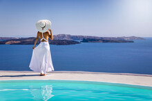 A Beautiful Woman In A White Summer Dress Stands By The Pool And Enjoys The Breathtaking View Over The Mediterranean Sea