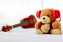 In Home Bedroom, Brown Lovely Fluffy Teddy Bear Toy Creatively Wearing Red Earphone And Sit On Bed Near Guitar As Lovely Doll For Enjoy Music Playing On Delight Celebration Holiday