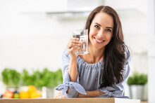 Smiling Pretty Woman Holds A Glass Of Water Leaning On Kitchen Desk