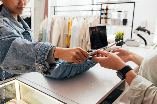 Female buyer giving clothes to unrecognizable clerk for checkout Fototapet