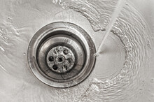 Water Flows Into The Stainless Steel Kitchen Sink Drain