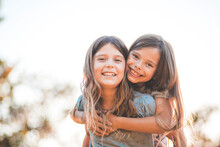 Portrait Of Two Little Smiling Girls Playing In Nature. Little Girl Carrying Her Friend.