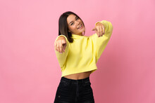 Teenager Girl Isolated On Pink Background Pointing Front With Happy Expression