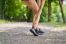 Achilles Tendonitis. Female Runner Holding Injured Achilles