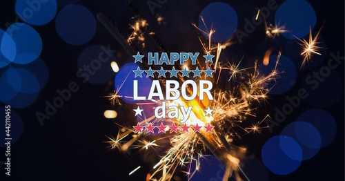 Composition of text happy labor day, with american flags and sparklers on dark blue with bokeh
