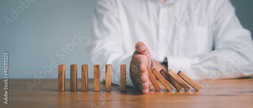 Fotografia, Obraz Risk and Strategy in Business, Hand stopping wooden block domino business crisis