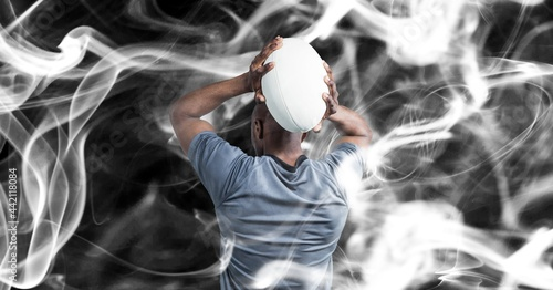 Composition of male rugby player holding rugby ball on black background