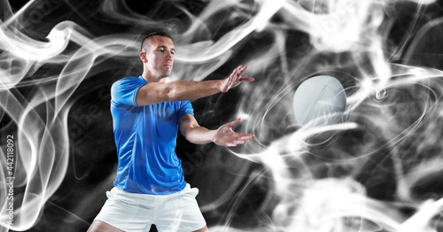 Composition of male rugby player catching rugby ball on black background