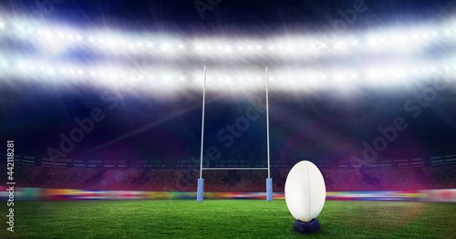 Composition of white rugby ball lying at stadium