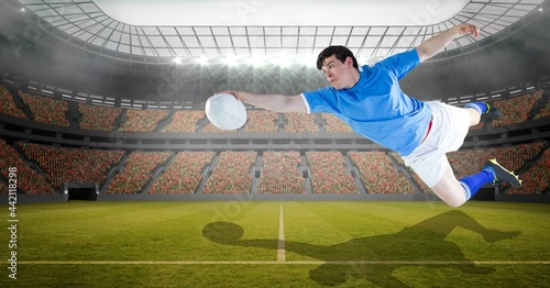 Composition of male rugby player holding rugby ball at stadium
