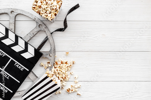 Movie film reel with clapperboard and popcorn. Cinema concept Fotobehang