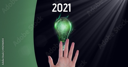 Composition of green copy space over year 2021, hand and lit green lightbulb, on black
